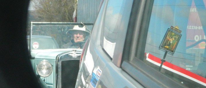 Old man in old car reflected in car mirror